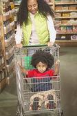 афро-американских мать, толкая молодой сын в корзину — Стоковое фото