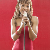 Portrait of woman singing with microphone — Stock Photo