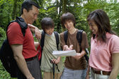 Family checking map while hiking — Stock Photo