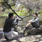 Man taking photograph on Asian woman in park — Stock Photo