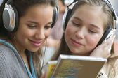 Close up of two teenage girls with headsets listening to music — Stock Photo