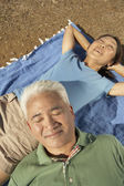 Senior couple relaxing on a blanket outdoors — Stock Photo