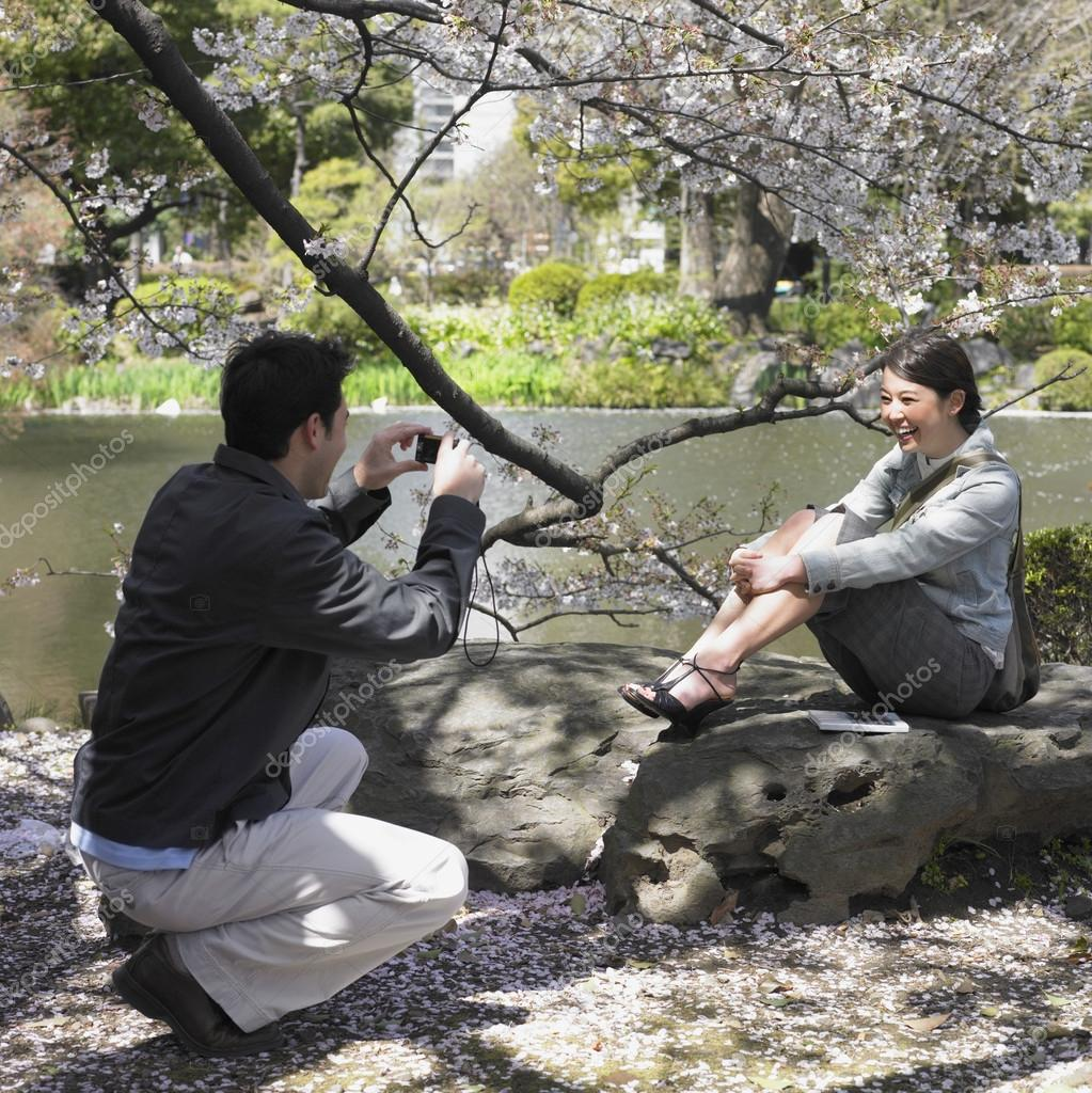 Man taking photograph on Asian woman in park — Stock Photo #13240054