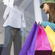 Asian woman with shopping bags window shopping - Stock Photo