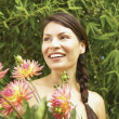 Portrait of woman holding bouquet of flowers - Stock Photo