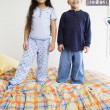 Brother and sister standing on bed together - Stock Photo