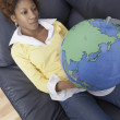 Woman holding globe armchair - Stock Photo