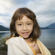 Portrait of girl wrapped in towel at lake - Stock Photo