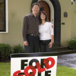 Foto Stock: Couple standing outside their new home