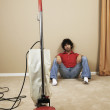 Young man resting during vacuuming - Stock Photo