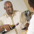 Man pouring wine for woman — Stock Photo