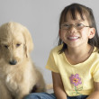 Portrait of young girl sitting with dog - Stock Photo