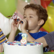 Boy blowing noise maker at birthday party — Stock Photo
