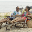 Senior couple lounging on beach with drinks - Stock Photo