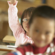 Young girl raising hand in classroom - Stock Photo