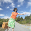 Young woman with a suitcase hitching a ride - Stock Photo