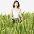Young woman meditating in tall grass — Stock Photo