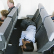 Businessman sleeping on airplane — Stockfoto