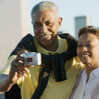 Senior couple taking pictures of themselves with city behind them — Stock Photo