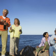 Extended family celebrate on rocky shore — Stock Photo