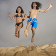 Couple jumping off sand — Stock Photo