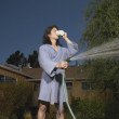 Man in robe watering grass — Stock Photo