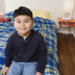 Boy sitting on bed — Stock Photo