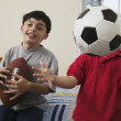 Portrait of brothers with soccer ball and football — Stockfoto