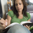 Teenager doing homework on subway — Stok fotoğraf
