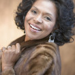 Portrait of African American woman wearing fur coat and smiling — Foto Stock
