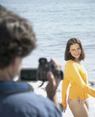 Couple with video camera at beach — Stock Photo