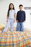 Brother and sister standing on bed together — Stock Photo