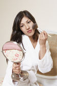 Woman in robe holding mirror and applying blush — Photo