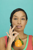 Portrait of woman holding tangerine — Stock Photo
