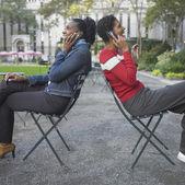 Vrienden praten op mobiele telefoon in park — Stockfoto