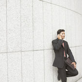 Businessman leaning against wall talking on cell phone — Stock Photo