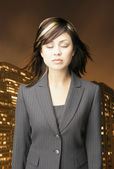 Businesswoman relaxing in front of city landscape — Stock Photo