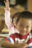 Young girl raising hand in classroom — Stock Photo