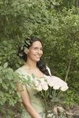 Joven mujer sosteniendo un arreglo de flores — Foto de Stock