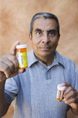 Portrait of man holding medication bottles — Stock Photo