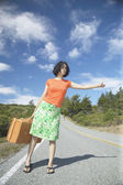 Young woman with a suitcase hitching a ride — Stock Photo