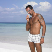 Man in swimming trunks and goggles kissing cross — Stock Photo