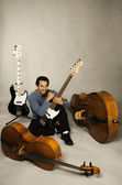 Man with collection of stringed instruments — Stock Photo