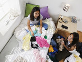 Young women sitting in piles of clothing — Stock Photo
