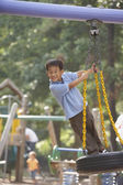Portrait of boy standing on tire swing — Stock Photo