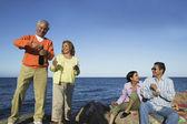 Extended family celebrate on rocky shore — Stock Photo