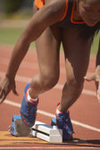 Female runner leaving starting blocks — Stock Photo