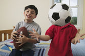 Portrait of brothers with soccer ball and football — Stock Photo