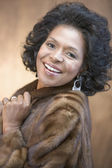 Portrait of African American woman wearing fur coat and smiling — Stock Photo