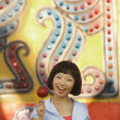Young woman eating a candy apple at a carnival — Stock Photo